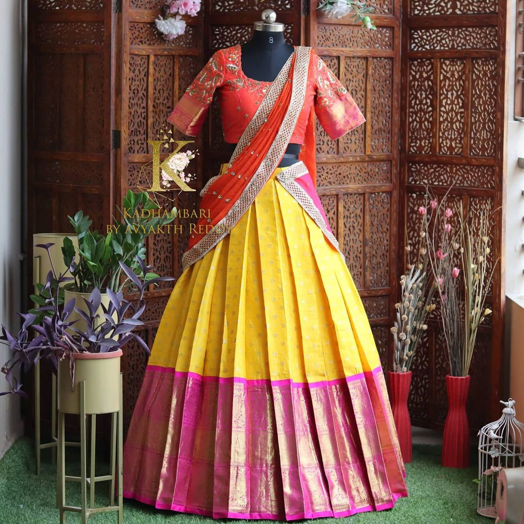 Traditional yellow pink color combination pattu langa and blouse with net dupatta. Blouse with hand embroidery work.  This outfit is Available at Rs 18000/- 2021-06-06