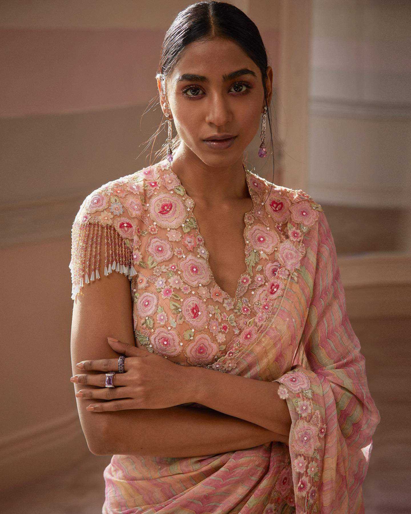 Pink Sunsets . Priti wears hand-painted soft pink georgette saree highlighted with zari and sequins. It comes with a detachable drape. The tulle blouse is enhanced with bloom motifs in resham and badla embroidery and has cap sleeves which are further elevated with fine crystals strings. 2021-06-07