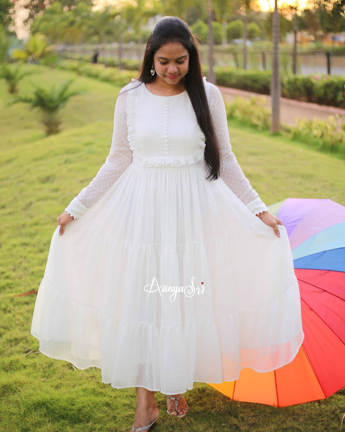 Vennela. Price :  RS. 2600/- White layered ankle length frock with ruffle and potlis detailing on the yoke . Comes with full sleeves and potlis on the sleeves and boat neck. 2021-06-09
