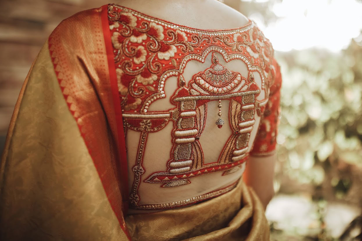 We call it  The doli blouse!  Stunning red color bridal blouse design with doli or pallaki hand embroidery maggam work on back.  2021-06-10