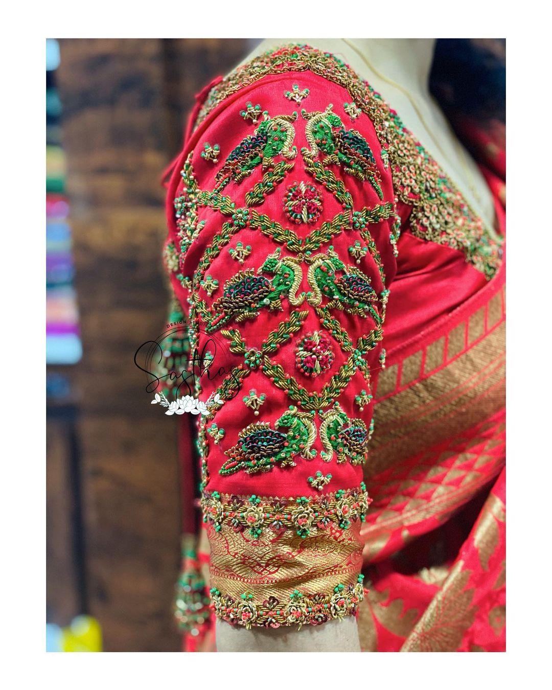 Stunning red bridal blouse sleeve with peacock benedictory aari work on sleeves.  2021-06-10