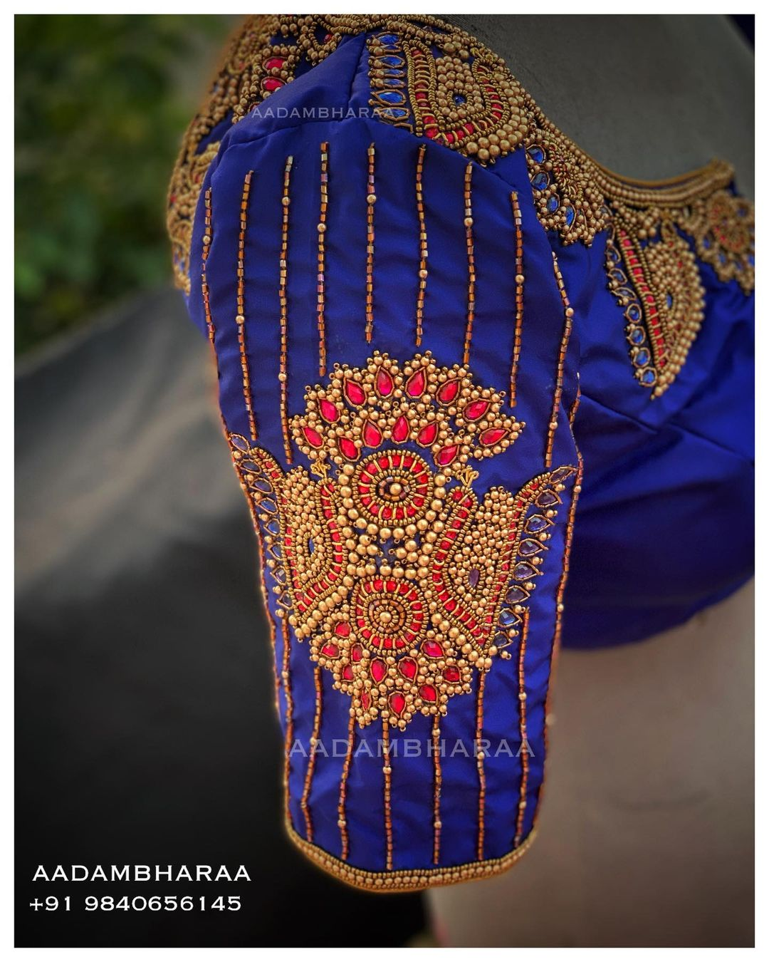 The blue blouse from Aadambharaa is intricately hand embroidered exuding grace and sophistication. The heavy Kundan work on the neck and back is sure to make you look like royalty on your big day. 2021-06-11