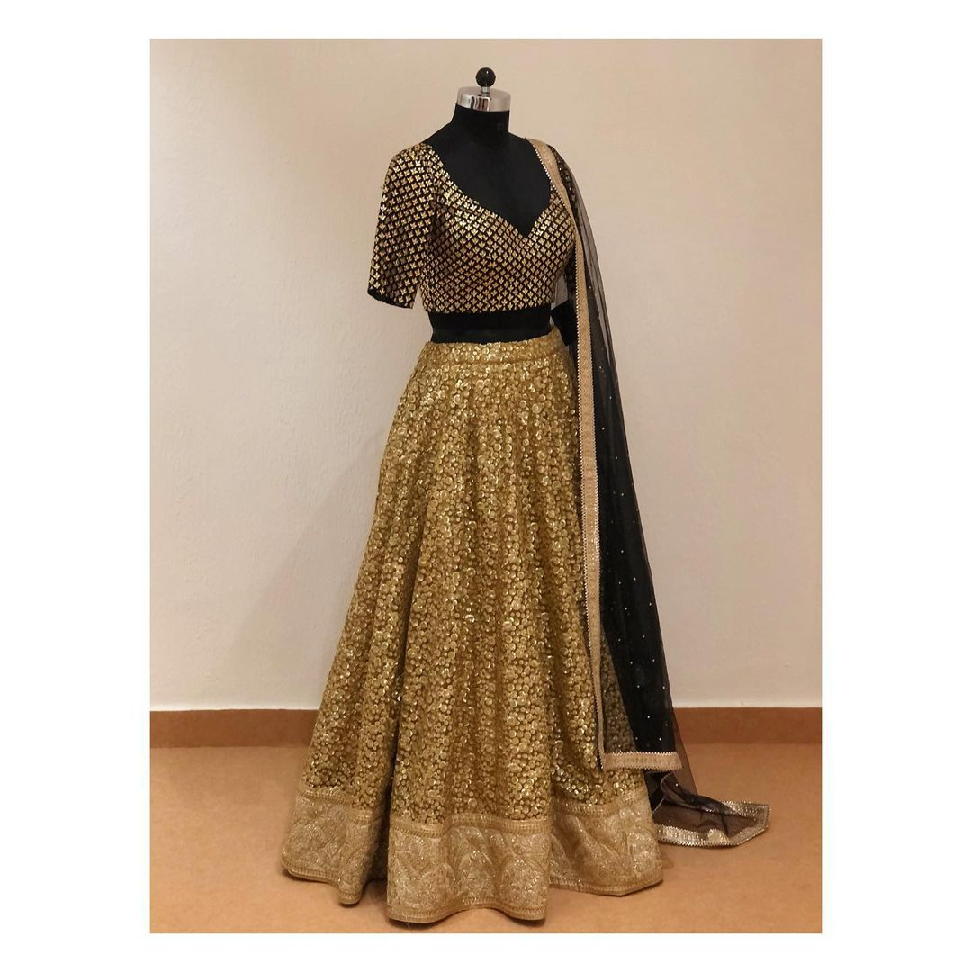 Gold sequins work lehenga with black kundan work blouse and black dupatta.  Blouse and dupatta color and style can be customised. For customisation  enquiry/order shivani@intricado.com or  Whatsapp:- +91 8527463626. 2021-06-15