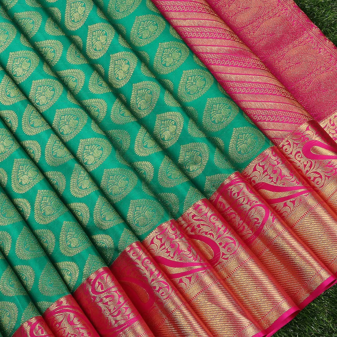 A Glorious shade of Sea Green and Bright Pink.  The design sensibilities in golden zari motifs of paisley and leaves.  Slant-designed zari lines and floral leafy branches in the border bring in the Poetic beauty of its intricacy.  Artfully Embellished  Cosmic Allure Kanchipuram Pattu Ensembles posing an array of exceptional masterpieces.  For Orders: +91 8142029190 2021-06-16