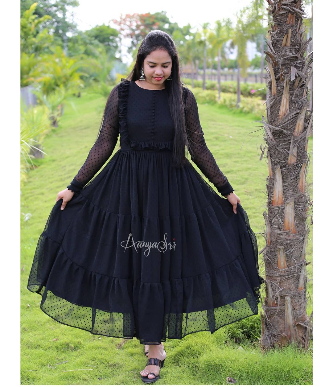 Black layered ankle length frock with ruffle and potlis detailing on the yoke . Comes with full sleeves and potlis on the sleeves and boat neck. Koyila. Price :  RS. 2600/- 2021-06-16