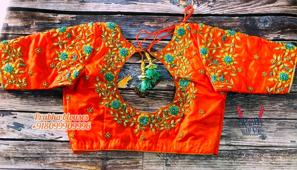 Gorgeous orange color bridal blouse design with floral and creeper hand embroidery gold thread and stone maggam work on neckline and sleeves.  2021-06-18