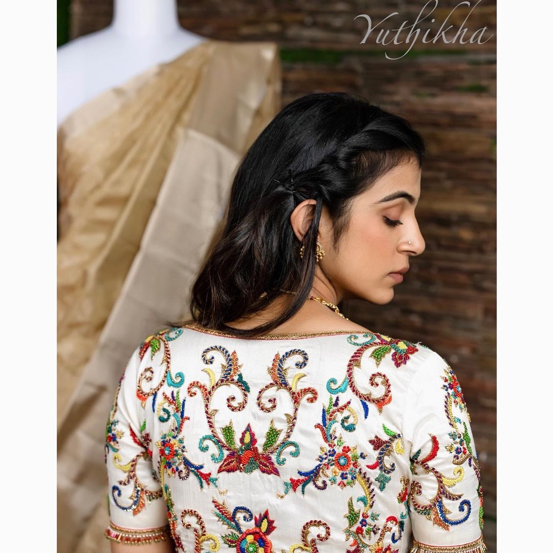 The floral designs with colourful embroidery . Stunning white color blouse with multi color floral hand embroidery maggam work.  2021-06-18