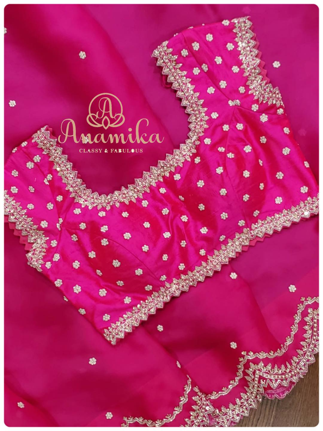 Bring home this stunning ensemble in lovely shade of hot pink hand crafted on satin organza. The silver zardozi work the scallop border the intricacy and captivating embroidery details – all add to create a stunning look on YOU!  An amazingly beautiful saree and blouse set that is a must for your next party