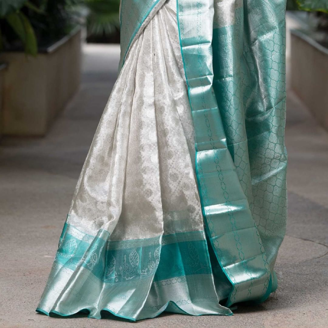 Beautiful silver kanjeevaram saree adorned by gorgeous Alekhya Harika.  The perfect zari work across the border is an absolute pick for your special day. The grand look is shown over you once draped royally. 2021-06-19