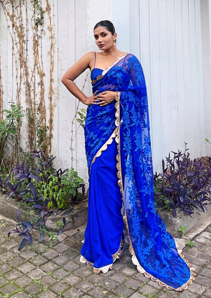 This is a heavily embroidered and sequin embellished soft net sari in azure blue. The base is a matching blue georgette. The border is a heavy hand worked scalloped border in gold sequin embroidery. The blouse is a azure blue raw silk. 2021-06-26