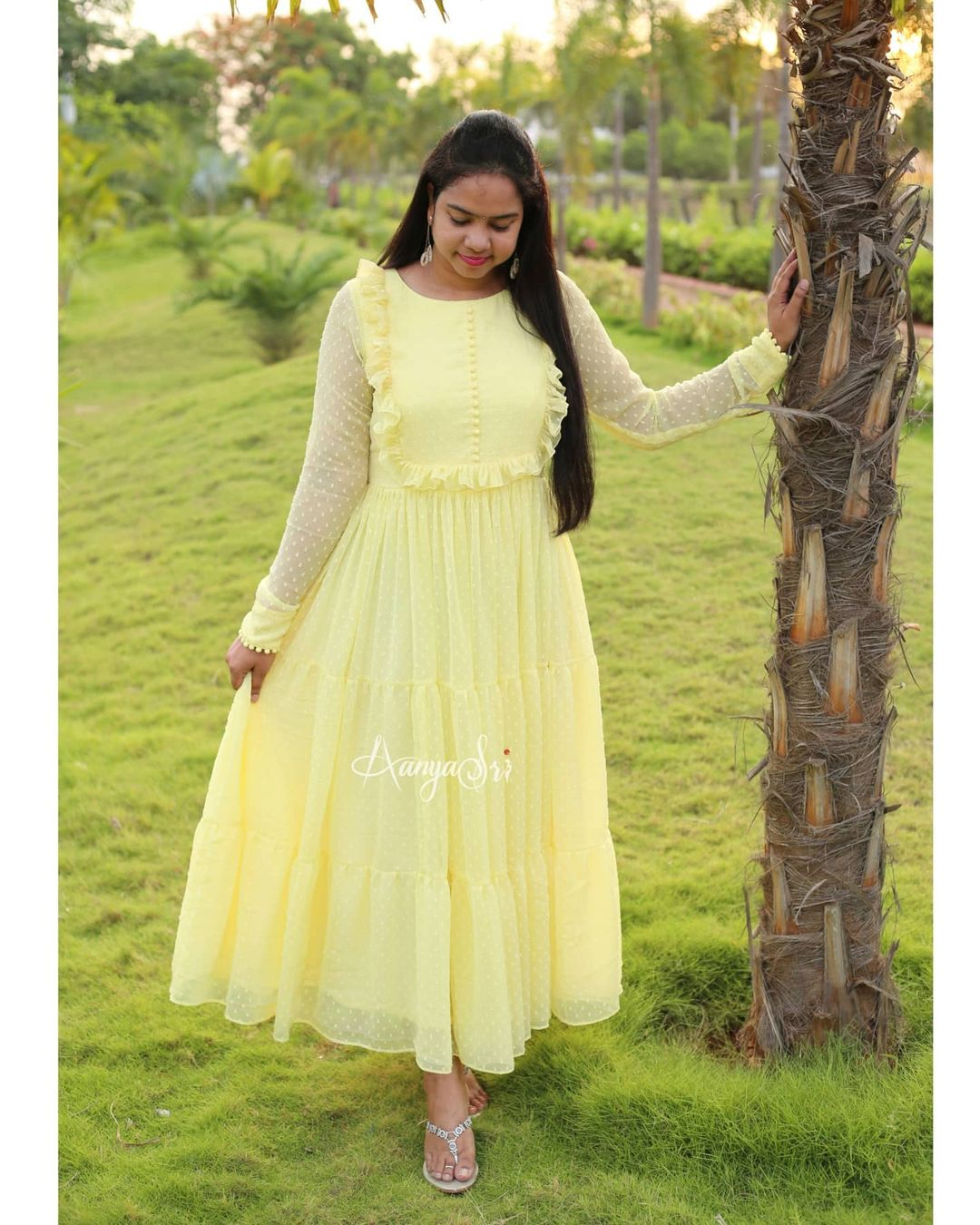 Pastel yellow layered ankle length frock with ruffle & potlis detailing on the yoke . Comes with full sleeves and potlis on the sleeves and boat neck. Price :  RS. 2600/- 2021-06-26
