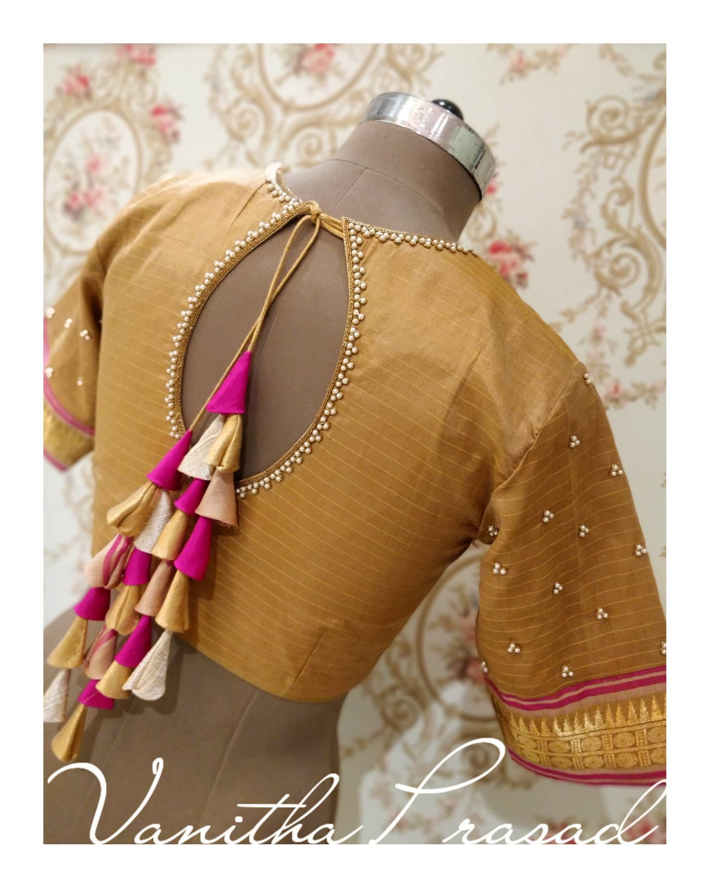 Pearl detailing covers the embellishment part while the bunch tassels add to the cheer. Beautiful gold shade blouse with pearl hand embroidery work and fabric tassels.  Blouse with key hole design. 2021-06-27