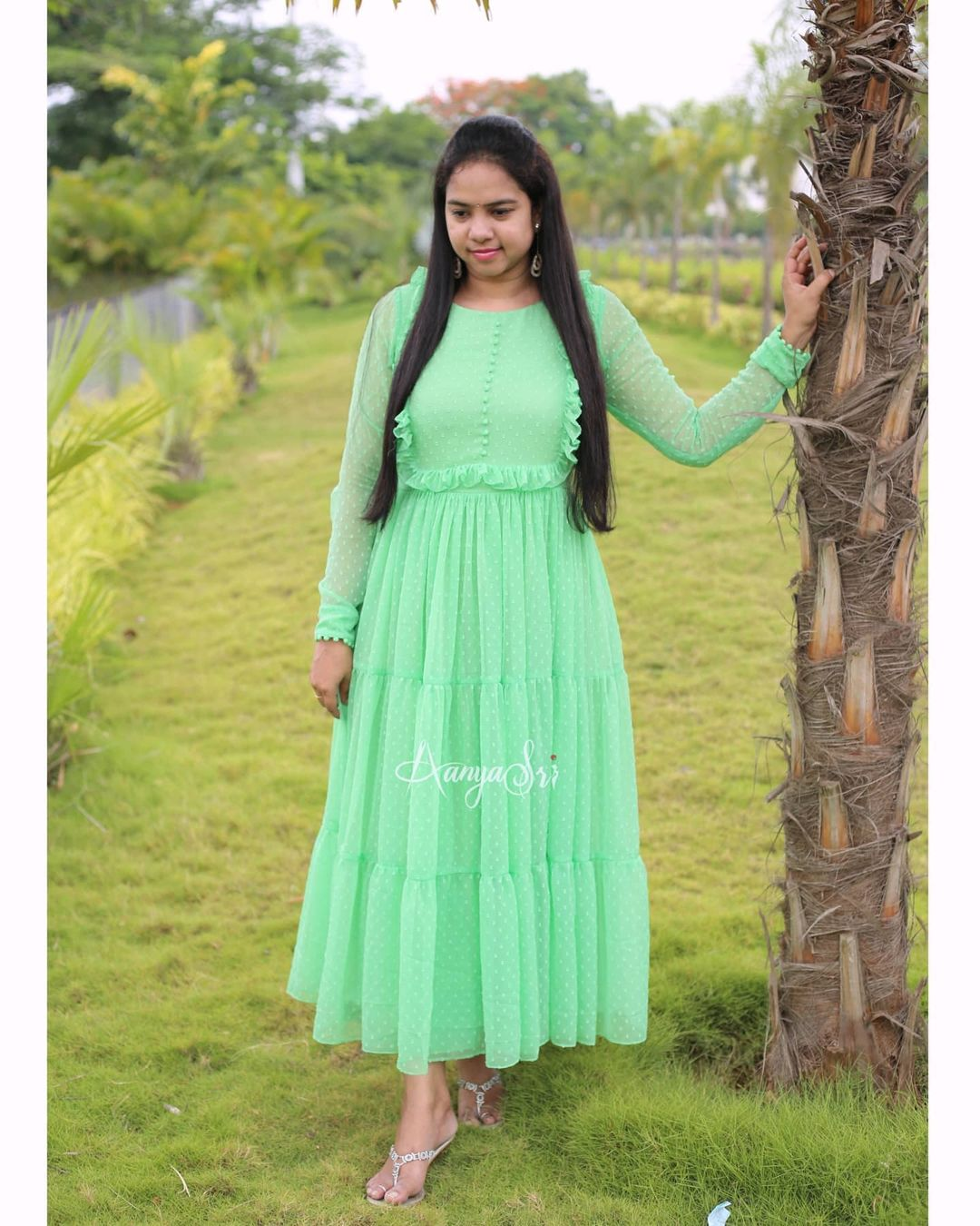 Sea green layered ankle length frock with ruffle & potlis detailing on the yoke . Comes with full sleeves and potlis on the sleeves and boat neck. Price : RS. 2600. 2021-06-28