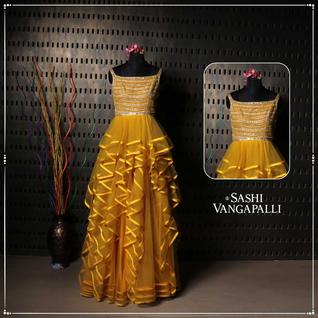 One of a kind flowy frilled attire adorned in the mustard yellow hues like a vision of fabulously folksy.  This ensemble made with intricate designs and finesse reflecting one's bright soul.  Our range of Indo-Western easy-to-go styles.  For Orders Contact: +91 9000777796 2021-06-30