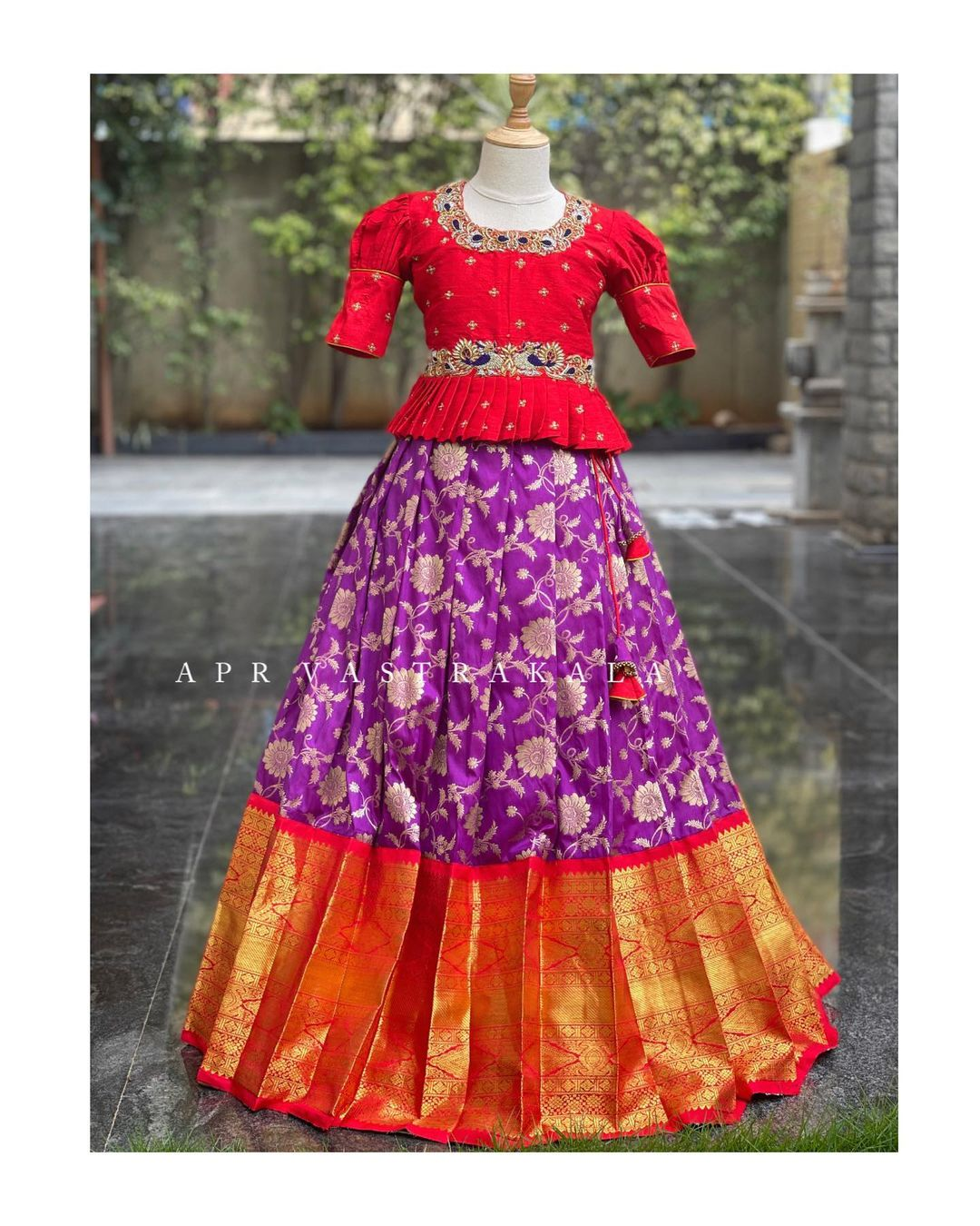 Stunning purple color kids pure kanchi pattu lehenga and red color pavada. Lehenga with big gold jari boarder. Long blouse with hand embroidery work on neckline and waist line.  2021-07-02