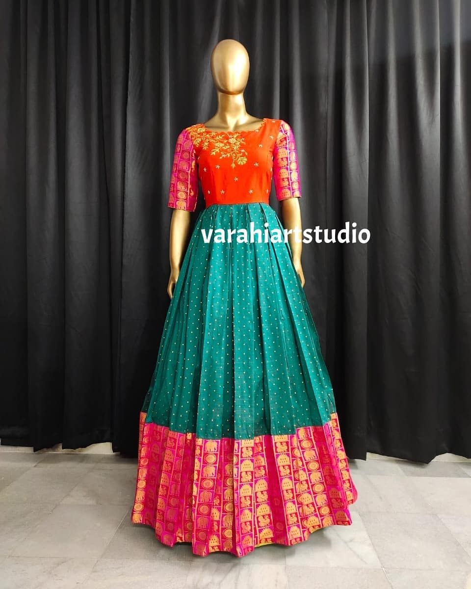 Beautiful powder green orange and pink color combination pattu long frock. Long frock with big zari boarder and sleeves. Long frock with hand embroidery work on yoke.  2021-07-04