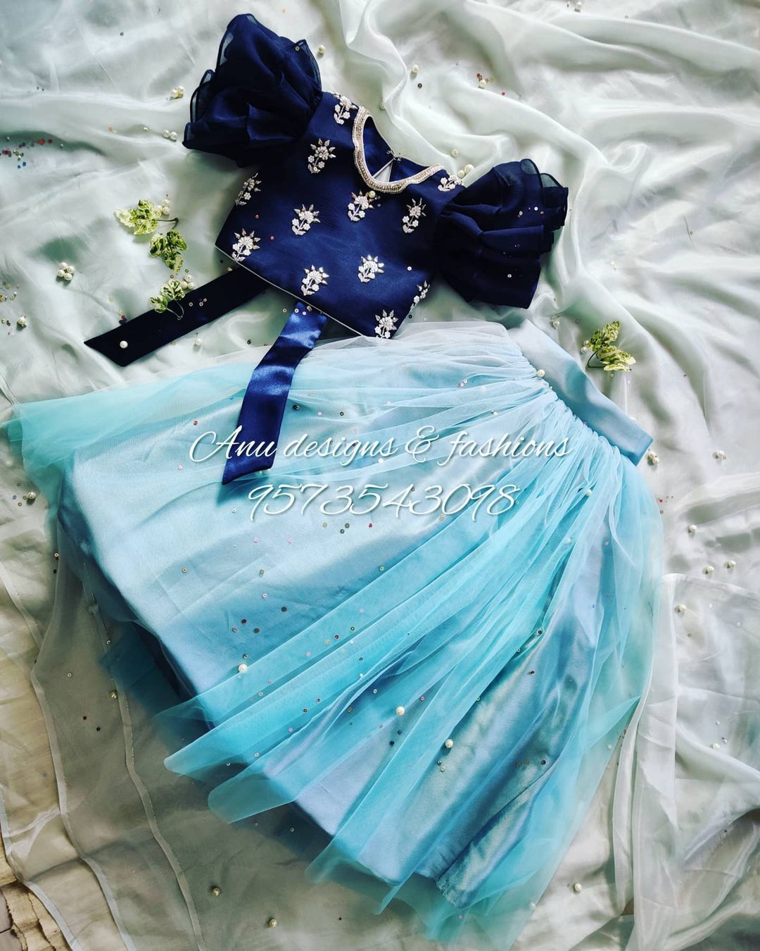 Stunning kids net lehenga and deep blue color ruffle sleeve blouse with hand embroidery work. 2021-07-09