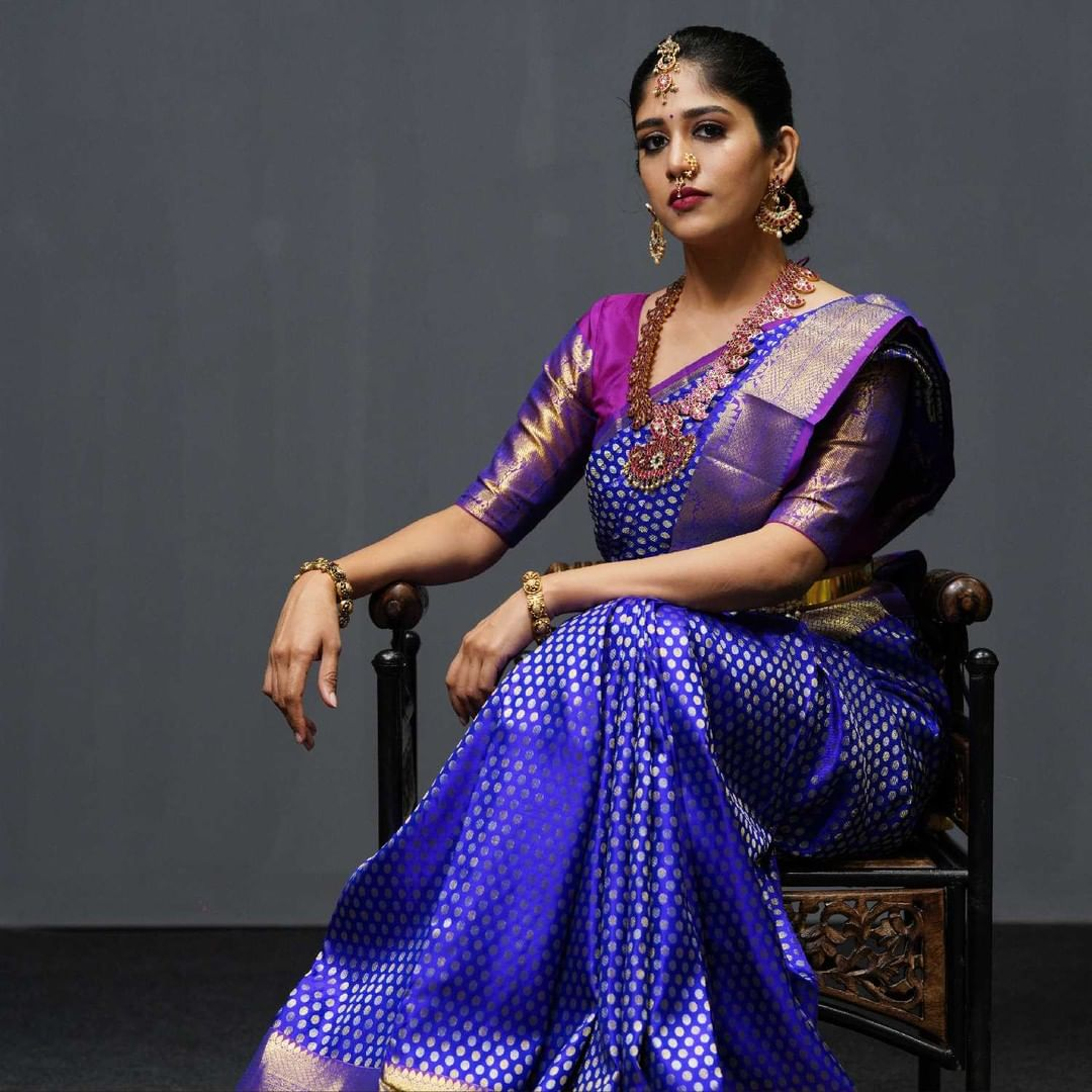 Beautiful Chandni chowdary in  royal blue kanchipattu saree which has polka dots with gold zari work all across the saree.  The border of the saree has intricate motifs with a combination of pink and gold zari weave which gives a royal look for your grand day.  Wear with style and grace the new collection of Mugdha.  Inframe Chandini chowdary. 2021-07-15