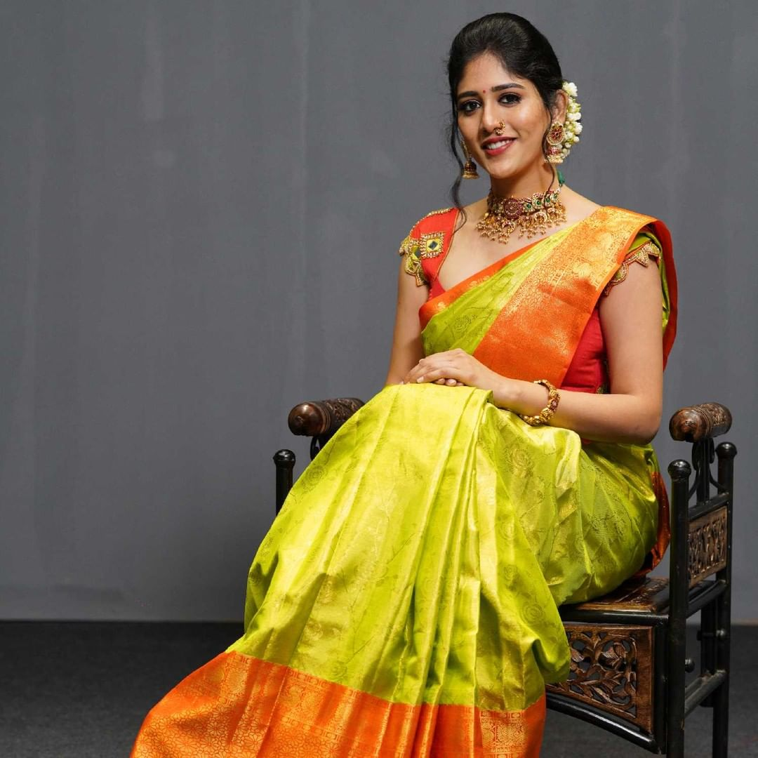 Beautiful Chandni chowdary in green kanchipattu saree.  This saree has beautiful flower motifs with a traditional orange border and gold zari work which is a perfect bridal look.  The grandeur of Gold emphasizes the look even more.  Wear with style and grace the new collection of Mugdha. 2021-07-15