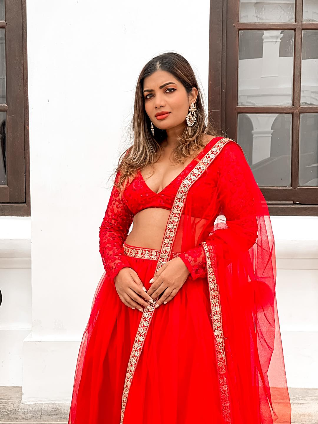 STARLET is  dream lehenga! It's princessy feminine and glamorous! It's a crimson red full tulle skirt double lined for a voluminous look adorned with a sequin embroidered waist belt. The blouse is fully thread work embroidered with red sequin embellishments in a floral design in red designed in a V-neck long sleeves style.  The dupatta is a soft net one with the matching gold sequin embroidered border in a floral design.  2021-07-16