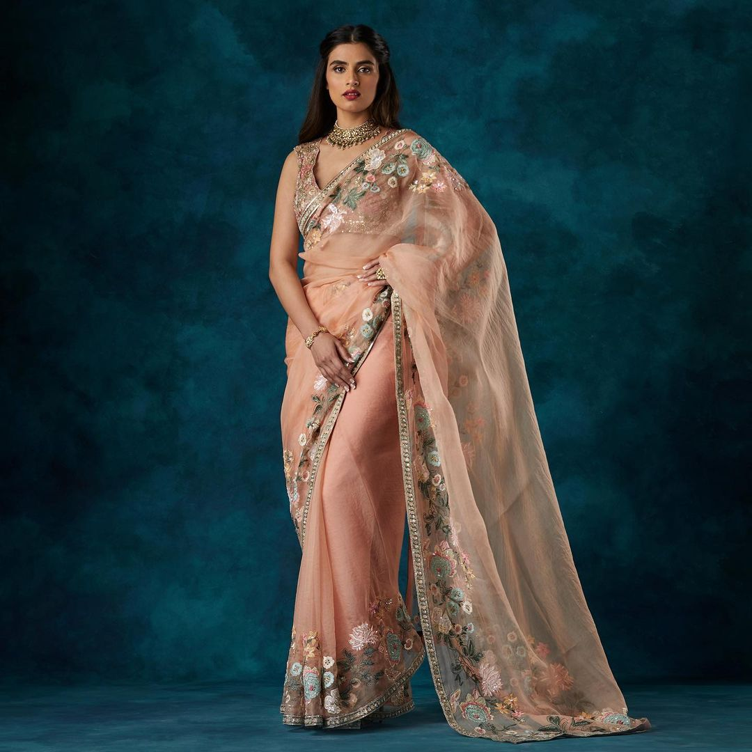 A dusky peach organza sari with a floating floral border embroidered in resham zardozi worn with a floral tulle blouse. Kindly WhatsApp  on +91-9833520520 for more information. 2021-07-21