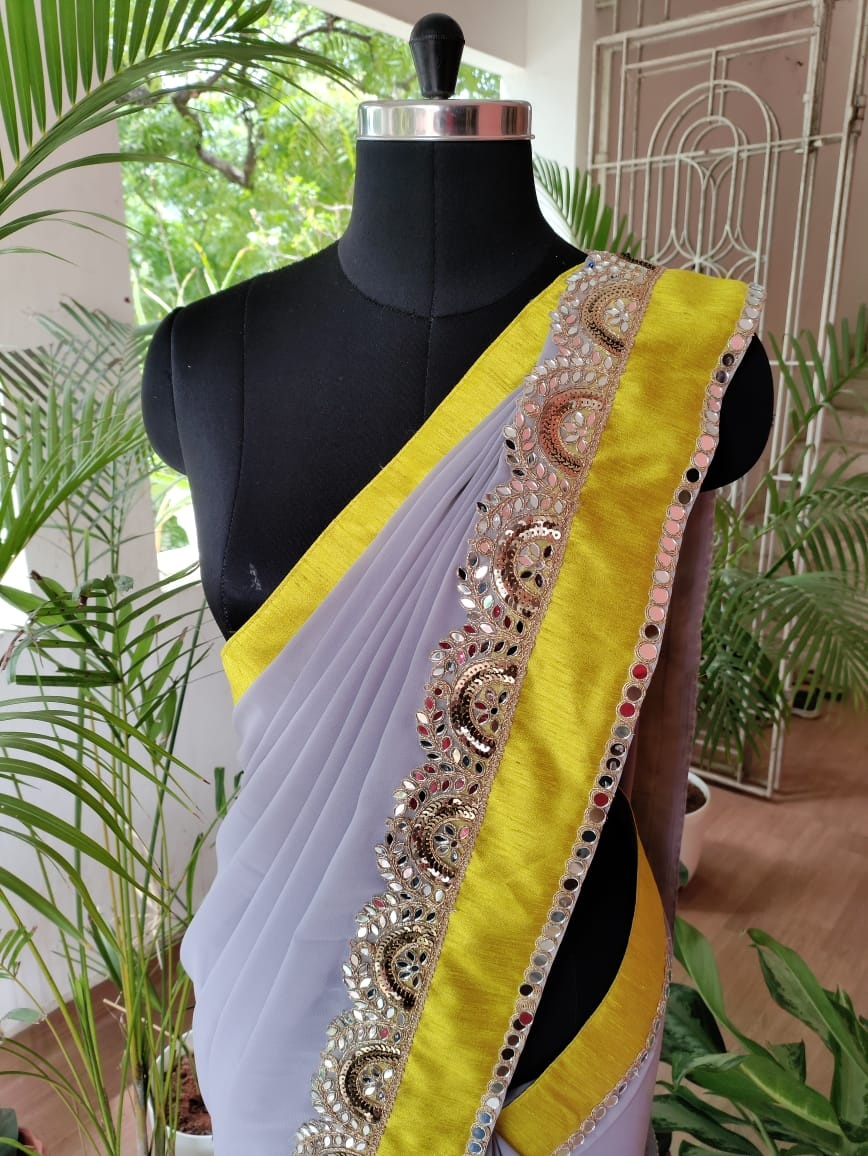 Grey Georgette saree. Flowy grey Georgette saree with contrast yellow border finished with mirror embellished border . . . Single piece available  Dm for orders  To customise your silk saree blouse pls whatsapp  on +91 9952093562. 2021-07-24