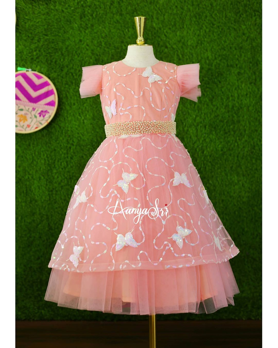Subtle peach butterflies embroidered kids frock with detachable skirt which comes along with handworked pearls waistline. Can be used in two different ways !! Price : RS. 2700 – RS. 4200. 2021-07-24