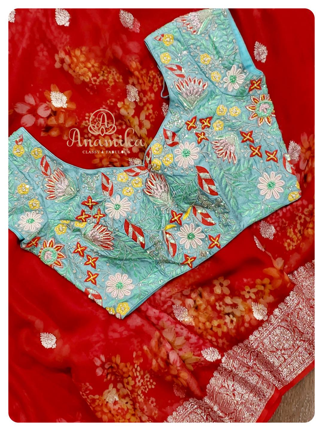 Vibrant blooms printed on this maroonish red banarasi chiffon saree. The luxurious feel of the saree the floral prints the silver zari border – all complement with one another to make this a must-have in your wardrobe.  What's more interesting is the blouse – contrast light blue blouse with exotic multi color hand embroidery embellished with pearls and cutdana… This sure will steal your heart. DM 360-545-3636 for inquiries 2021-07-31