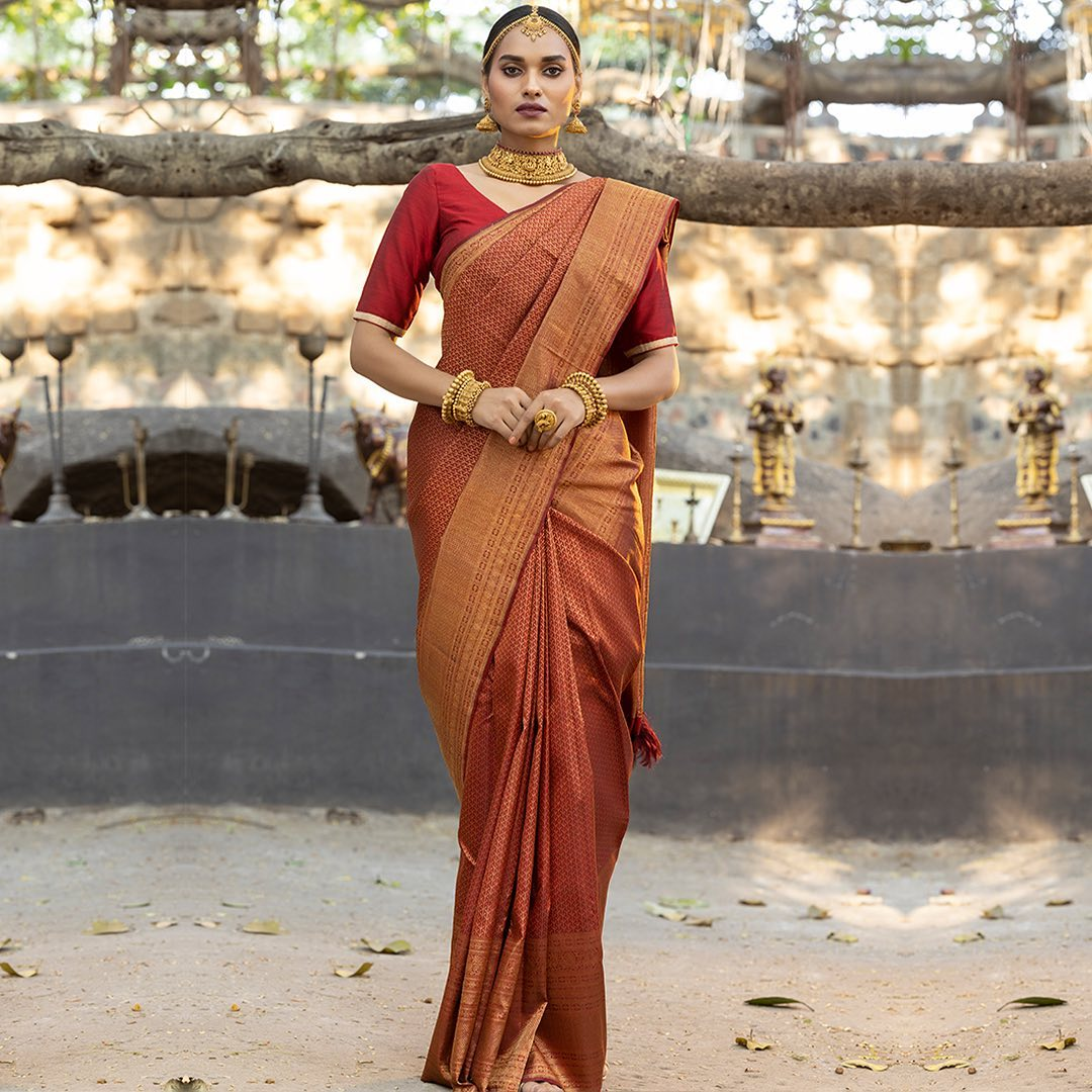 While any of the magnificent handwoven Kanchipuram silk sarees may enthrall wearers and captivate admirers this desirable saree made from pure silk and dyed in Barn Red  has even more to offer. Intricately hand woven with precise motifs all over this beguiling yard from Samyakk's newest arrival narrates a beautiful tale of authentic craftsmanship and Indian Heritage. 2021-07-31