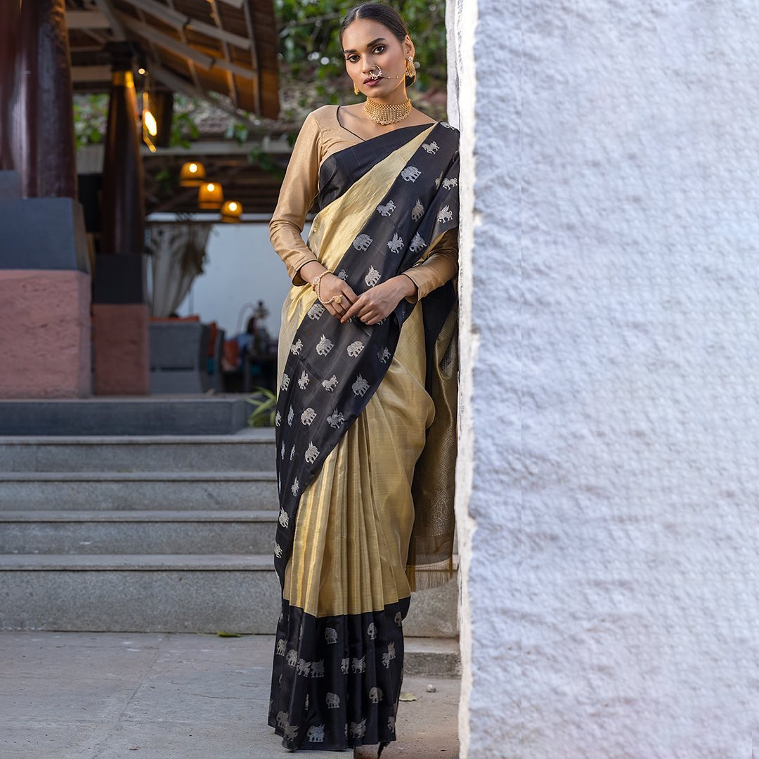 With the fabric narrating a tale of royalty this gold and silver dual-tone Kanchipuram Tissue saree exhibits the exquisite blend of german silver and authentic 2gms of gold handwoven to the perfection for the perfect you to flaunt at any wedding occasion or a grand celebration. Hand-pick this beguiling beauty that features kuthirai (horse) and yanai (elephant) designs on dramatic black borders  contrasting with the body and are sure to catch the eye. 2021-07-31