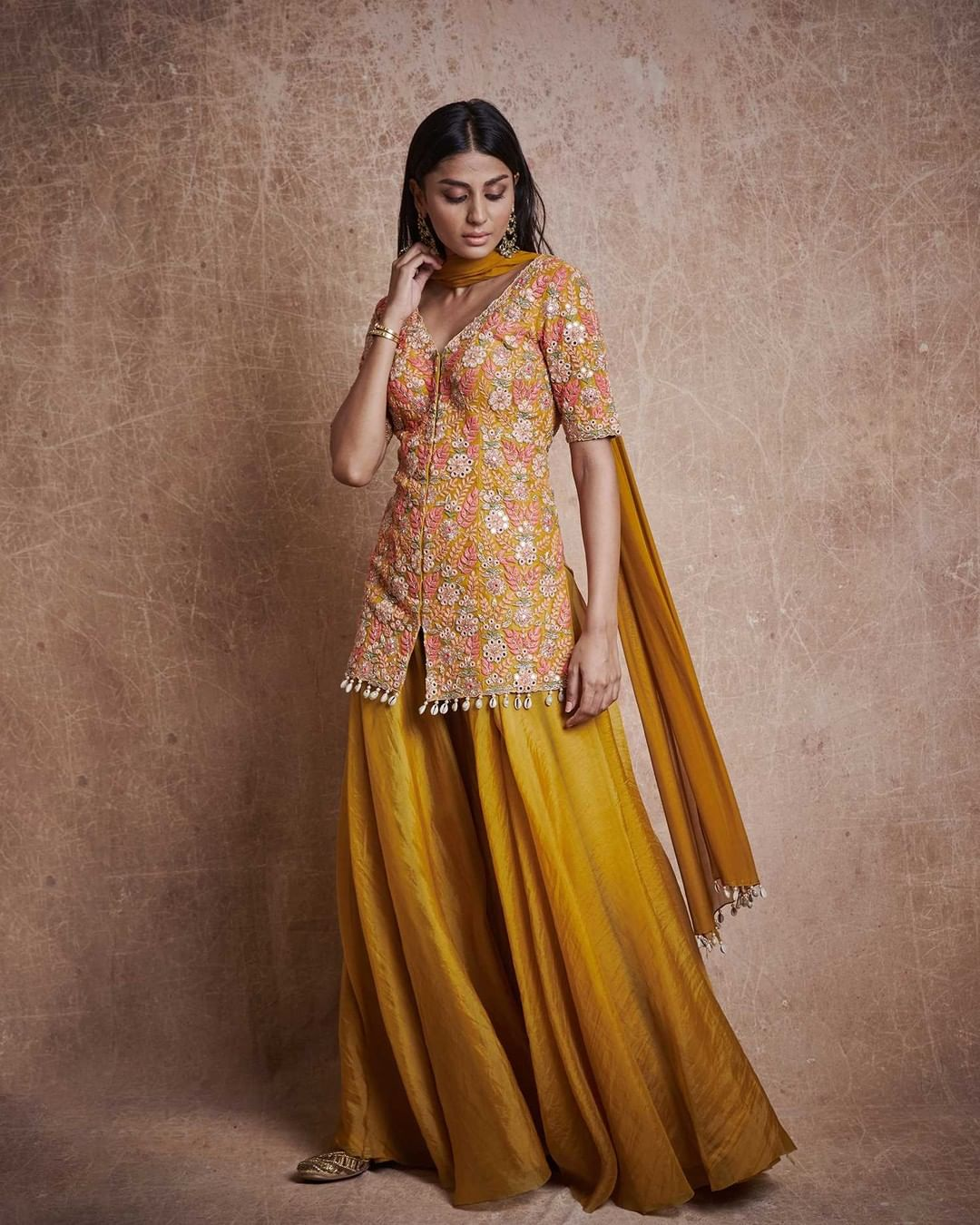 Festivities are incomplete without the mellowness of yellow! Find yellow treasure in Camel tiered sharara with fan flower embroidered kurta with cowrie shell detailing and chiffon dupatta.   For further enquiries please connect with  team on +91 7506633202 via call or WhatsApp. 2021-07-31