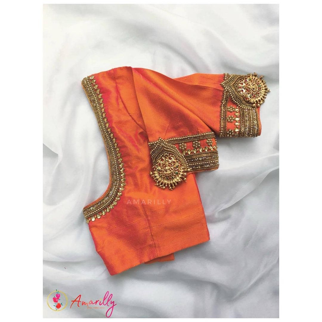 Stunning orange shade designer blouse with chaandbali vanki design hand embroidery work on neckline and sleeves.  2021-07-31