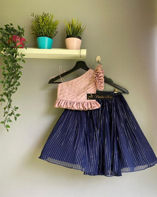 A beautiful navy blue skirt with silver lines on it teamed with a beautiful blush pink one shoulder blouse for girls from the house of Vinisha rao designer studio !! Suitable for all kind of occasions for your little @munchkins!! .. . You can call  to order on Contact : 9704994151. . Email - shopvinisharao@gmail.com. 2021-08-01
