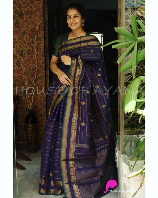 Kanjivaram pure silk handwoven saree with zari designs all over completed with bottle green selvedge and double paet borders. Midnight blue silk blouse plain with coordinated borders (as shown in last image) The saree comes with its own blouse piece. The one worn by the model is for styling purpose only.  2021-08-02