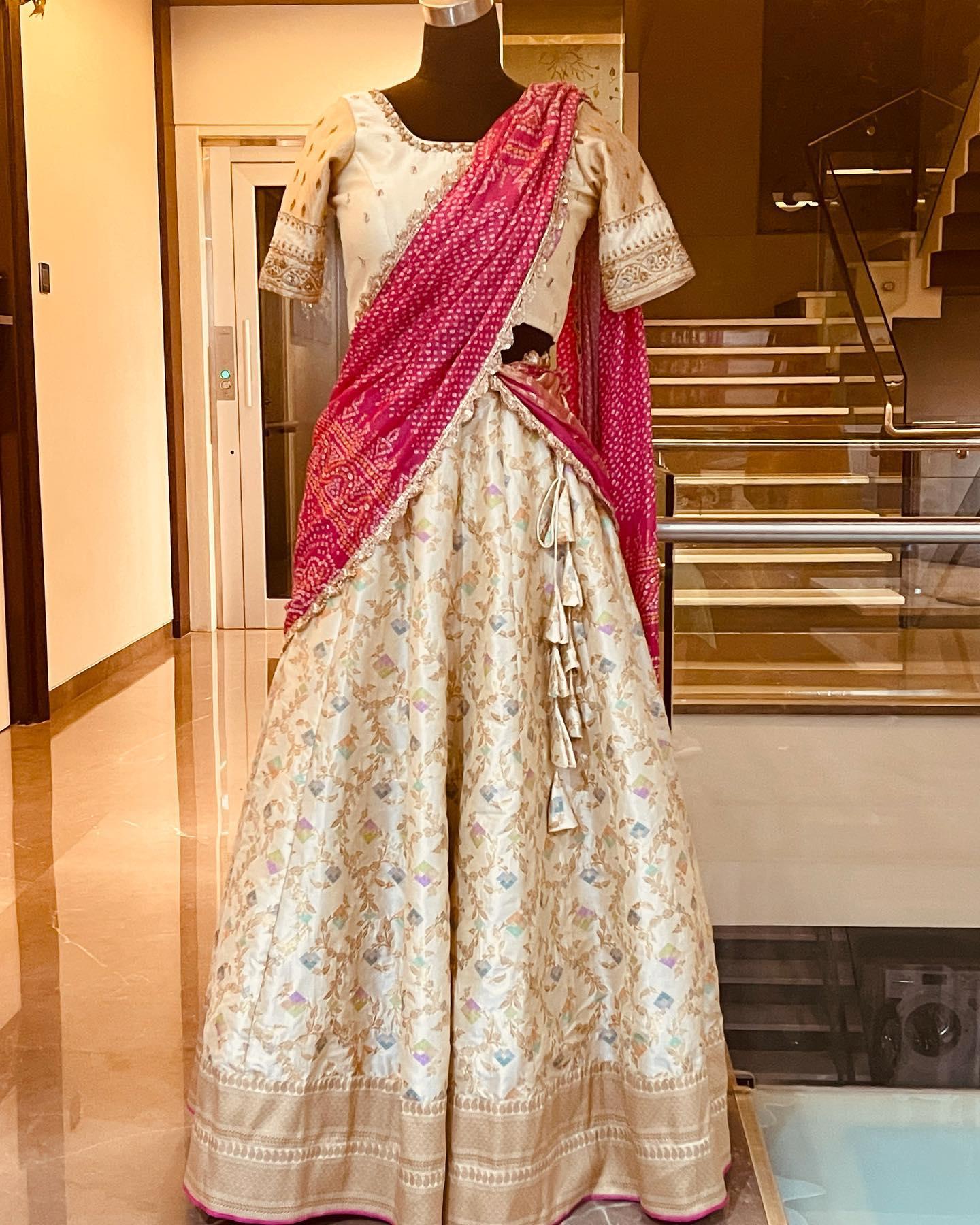 Beautiful off white color benarasi lehenga and blouse with pink color bandhini dupatta. Price : 15500 INR.  To order WhatsApp 7013728388. 2021-08-26