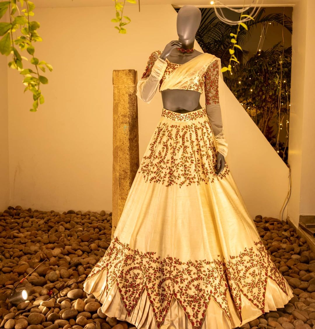 Intricately embroidered floral couture lehenga . Finely embroidered with glass beads in shades of ruby red and emerald green  with pleated satin finish and a sheer dupatta. 2021-08-27