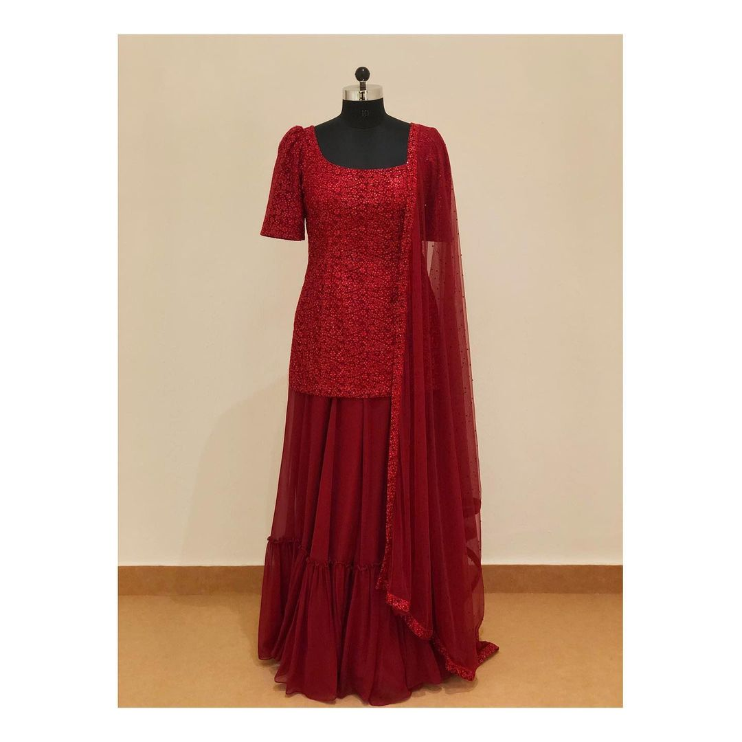 Deep red puff sleeved sharara suit with thread and sequins work.  For enquiry email at shivani@intricado.com  or Whatsapp at +918527463626 2021-08-30