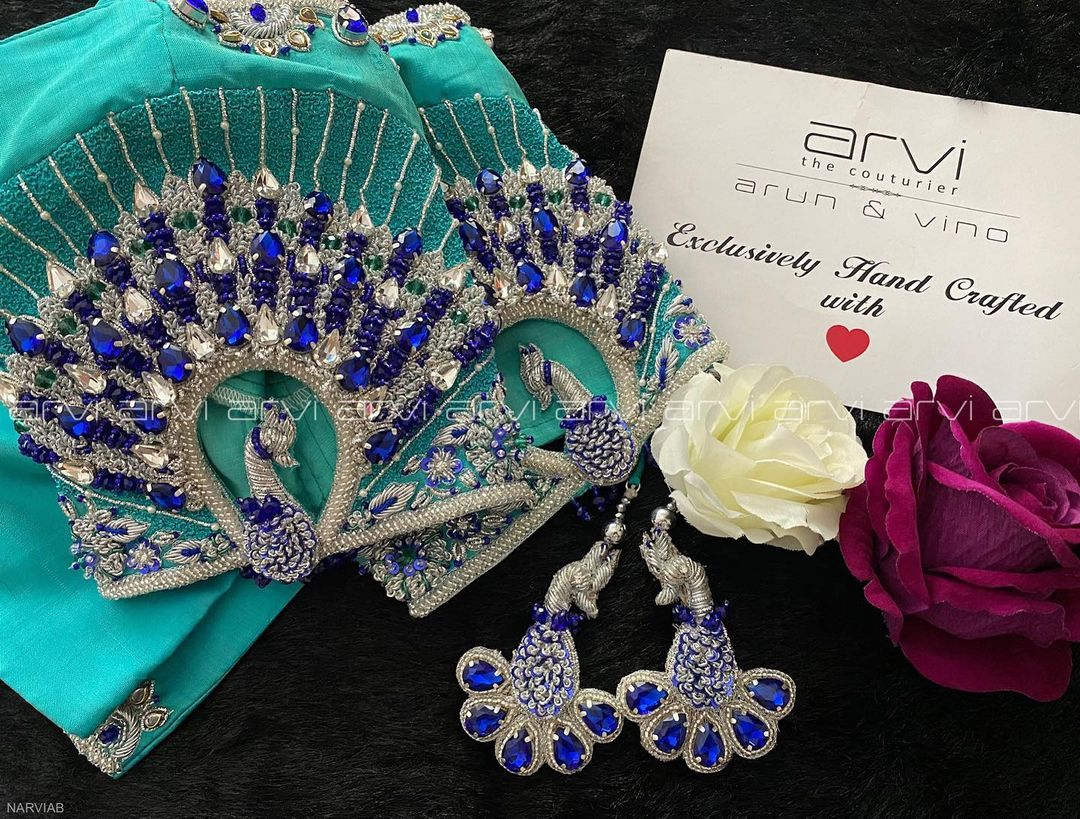 Stunning cyan color bridal blouse hand with peacock hand embroidery silver thread and multi color stone aari work.  2021-09-02