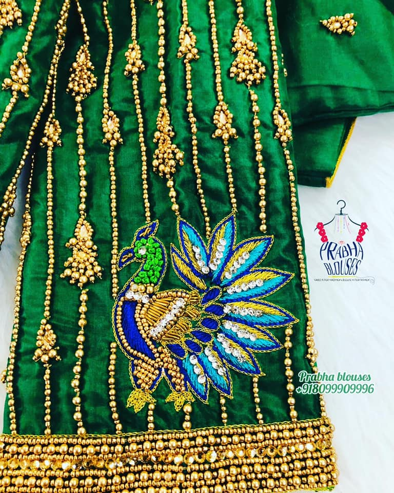 Stunning bottle green color blouse with bead aari work. Blouse with contrast blue thread peacock maggam work on sleeves. 2021-09-03