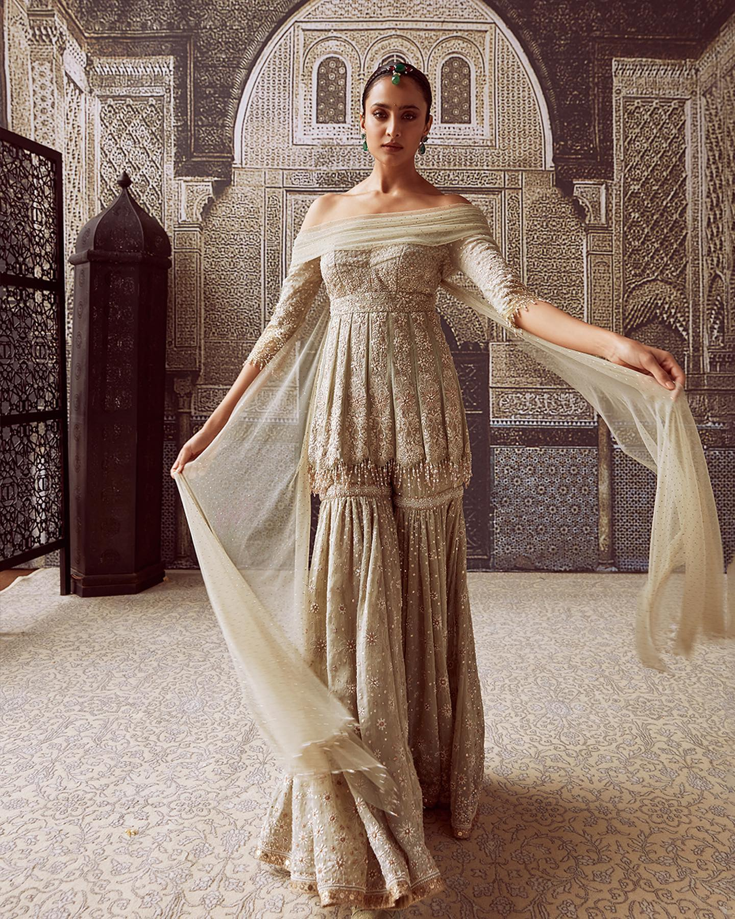 Sonali is seen here in  chikankari-embroidered short kurti in jade tissue-georgette that comes with a 14-kali matching sharara.  An off-shoulder draped neckline and attached tulle wings add to the playfulness.  2021-09-05