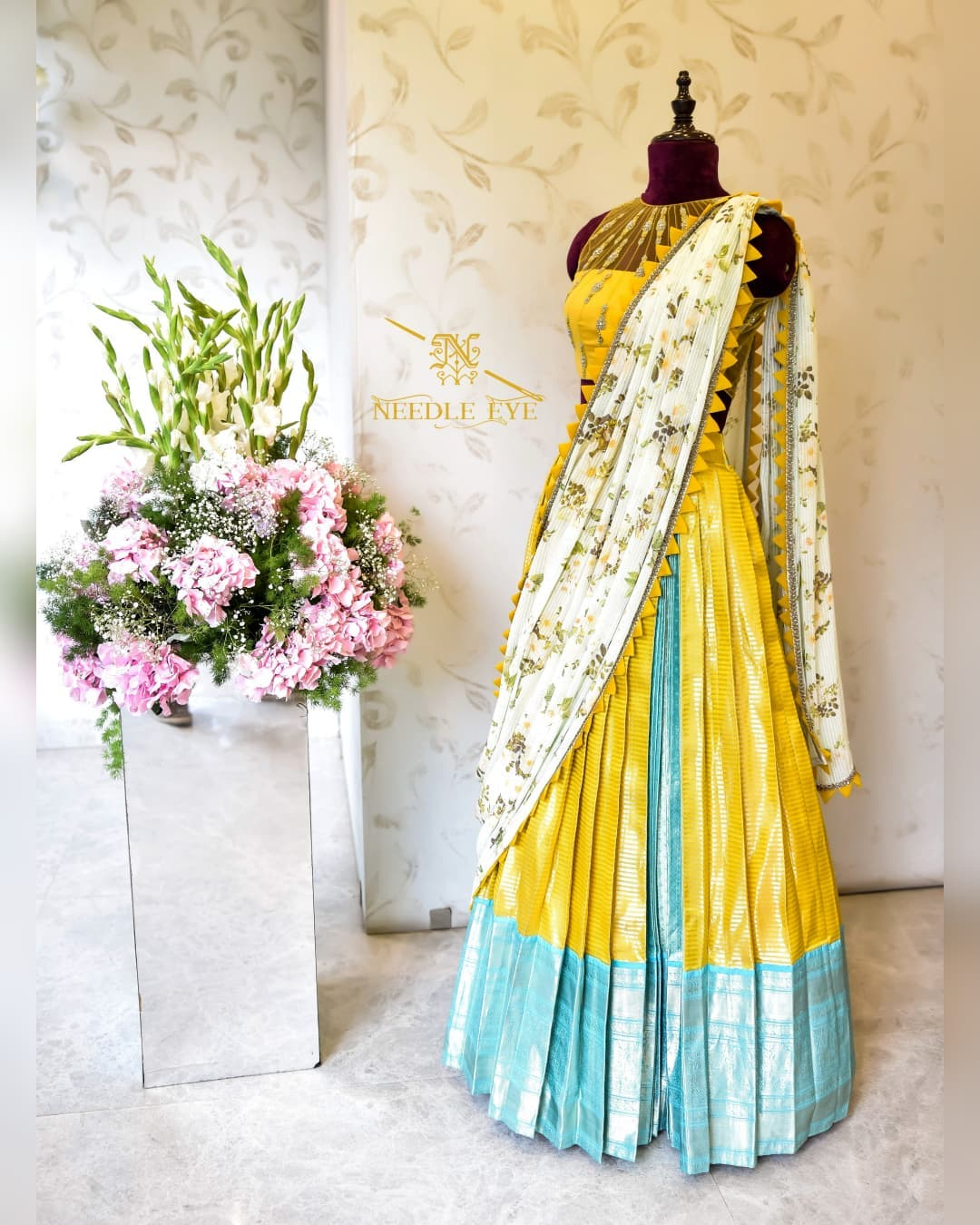 Bright yellow color pure silk skirt and netted sleeveless blouse is paired with floral Georgette dupatta