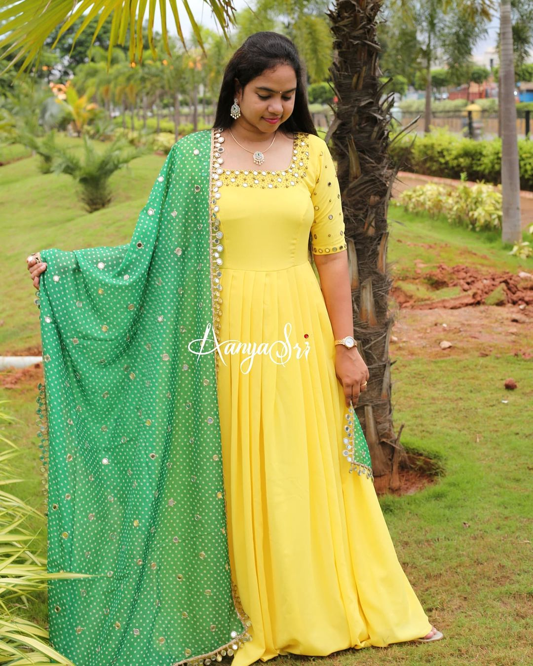 Yellow long frock with intricate real mirrors work on the yoke and sleeves paired with an elegant mirror worked green colored bhandini dupatta. 2021-09-08