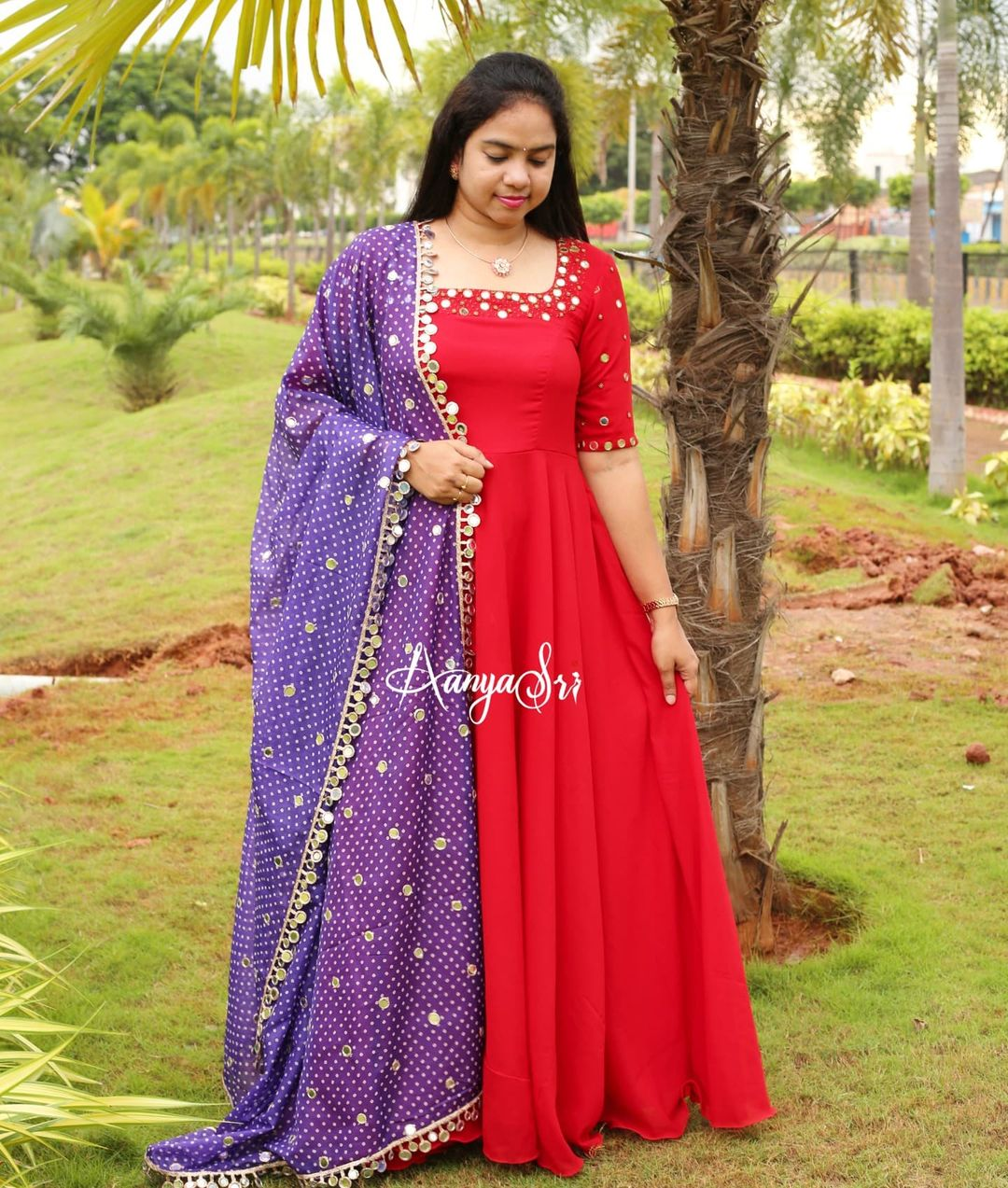 Red long frock with intricate real mirrors work on the yoke and sleeves paired with an elegant mirror worked green colored bhandini dupatta. 2021-09-08
