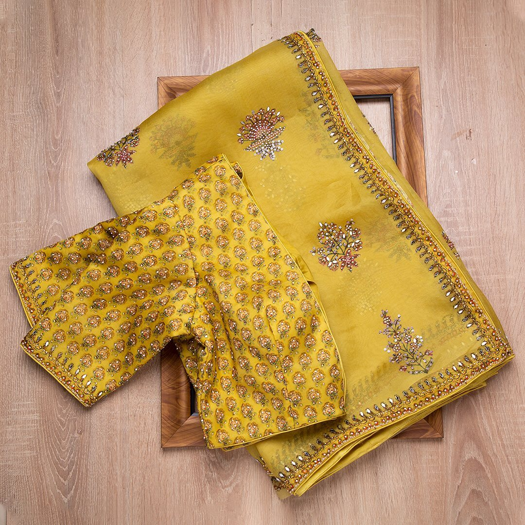 The graceful serenity of organza hued in royal yellow is accentuated with embroidery details creating beautiful motifs all over the drape is an artful masterpiece. A printed ready-blouse with sequins augmentation is a complete celebratory ensemble.  - Worldwide free shipping Contact : 00919845922959 Email: Esales@samyakk.com Product Code: SE2453 2021-09-09