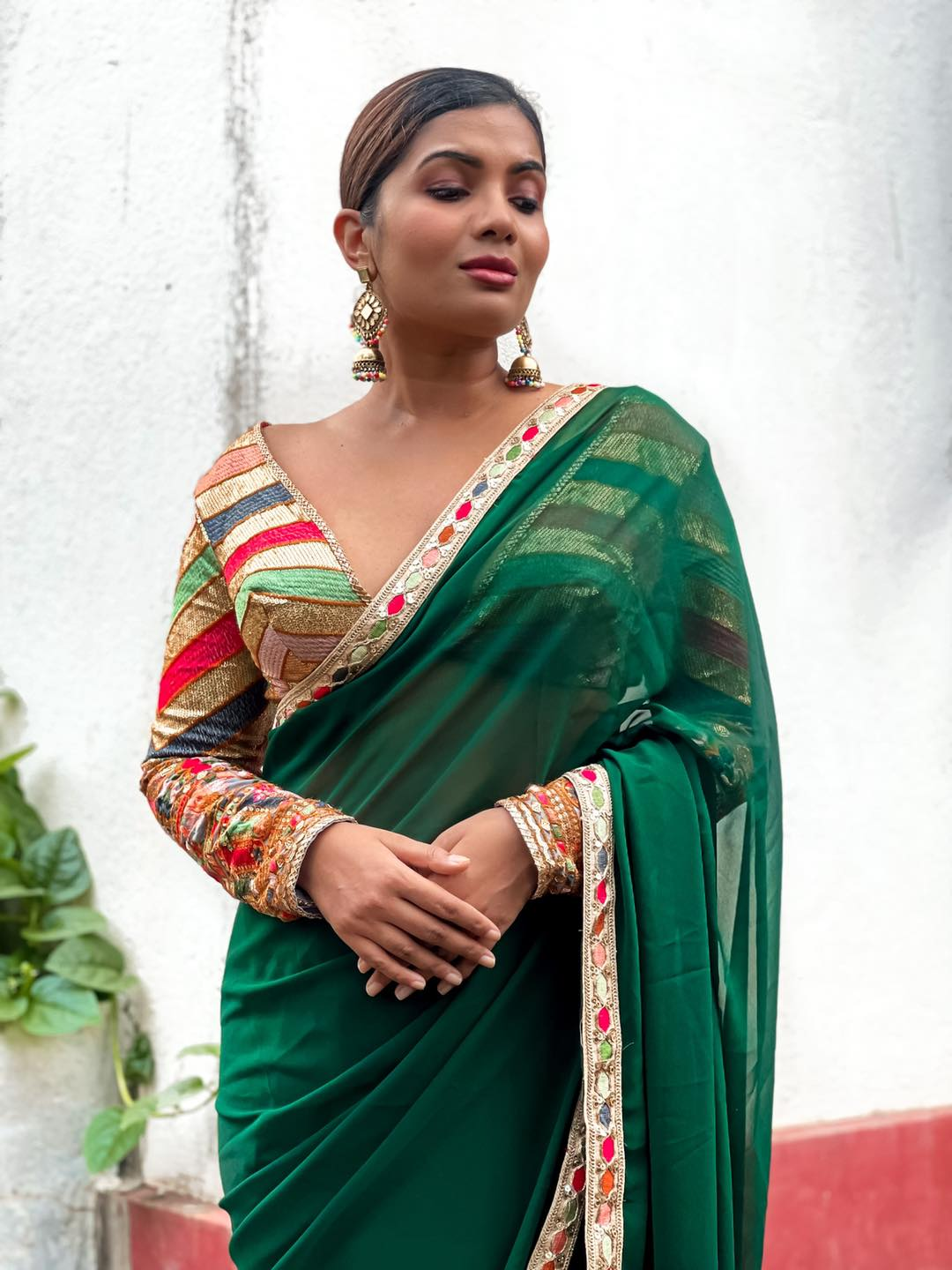 LEELA. Pure perfection in a sari! This is a deep emerald green georgette sari with a beautiful thread work sequin embroidered border in multi colors.  the blouse is a beautiful fully embroidered fabric with thread work and sequin work. The multicolor chevron and floral embroidery mix presents a beautiful juxtaposition of designs.   2021-09-11