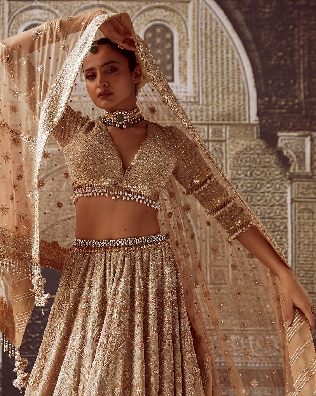 Sonali is wearing 16 kalis chikankari lehenga made in tones of green and pink on ivory. It is paired with a V-neck blouse with layered sleeves and a matching tulle dupatta with crystal detailing.  2021-09-11