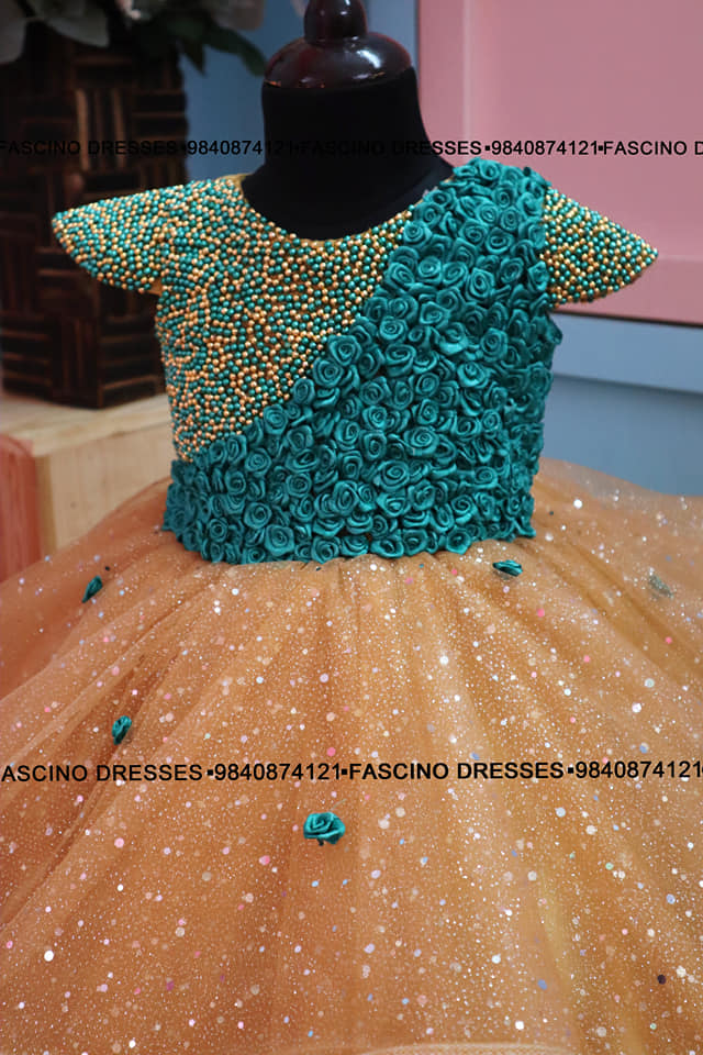 Golden shimmer gown with peacock color handcrafted bodice embellished with tiny flowers . A classy creation from #Fascino