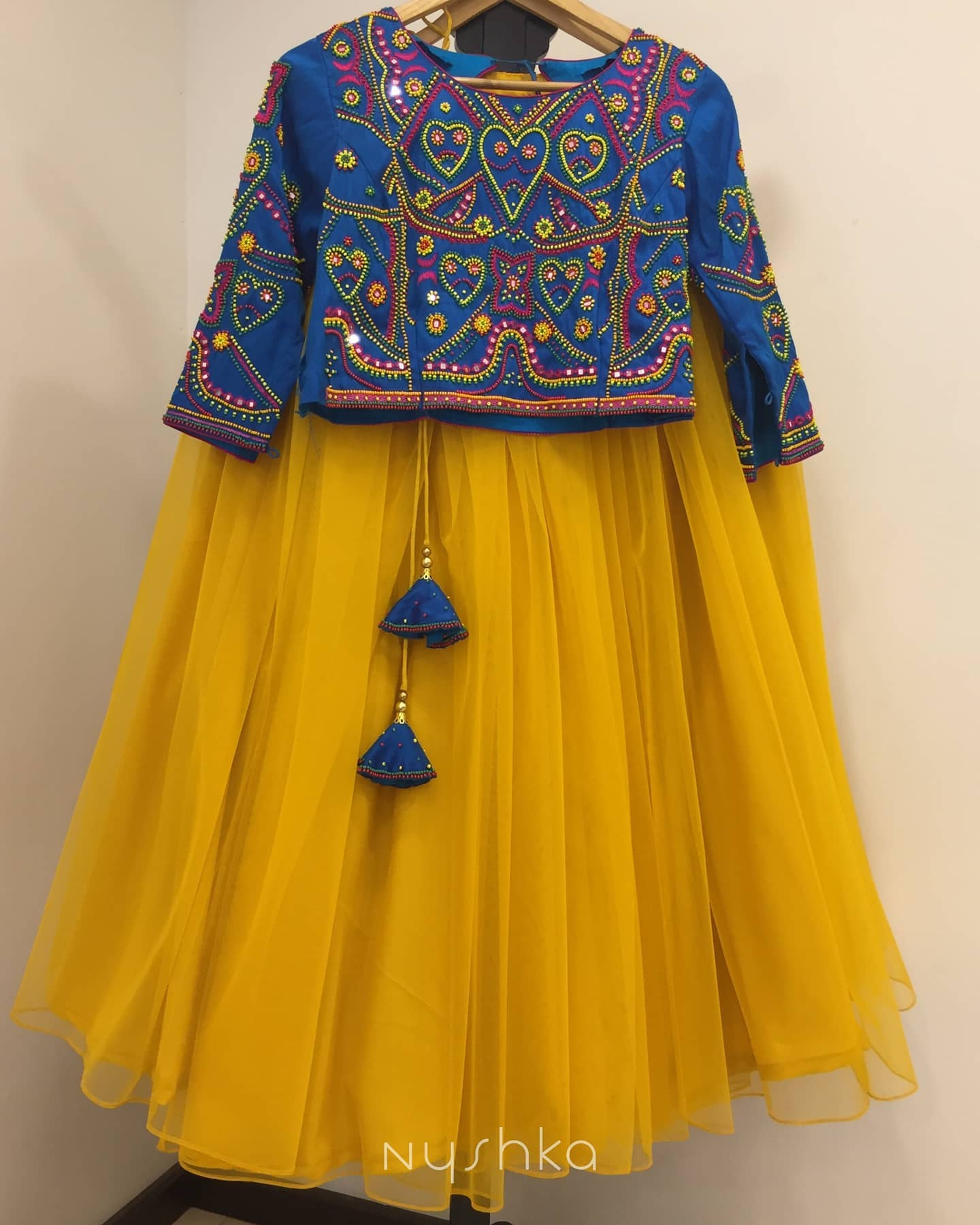 Shine your brightest in this vibrant yellow lehenga. Beautiful yellow net skirt and blue crop top with hand embroidery work.  2021-09-15