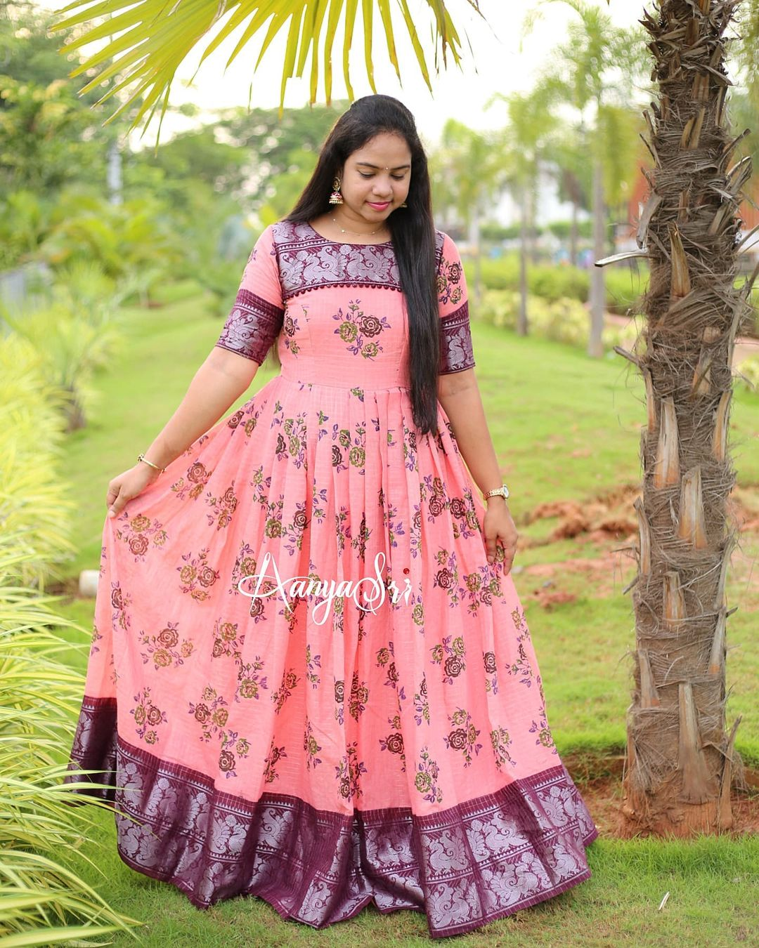Peach floral maxi with silver zari checks all over and a brown border. Comes with potlis detailed yoke.  Perfect for the upcoming festive season ! 2021-09-15