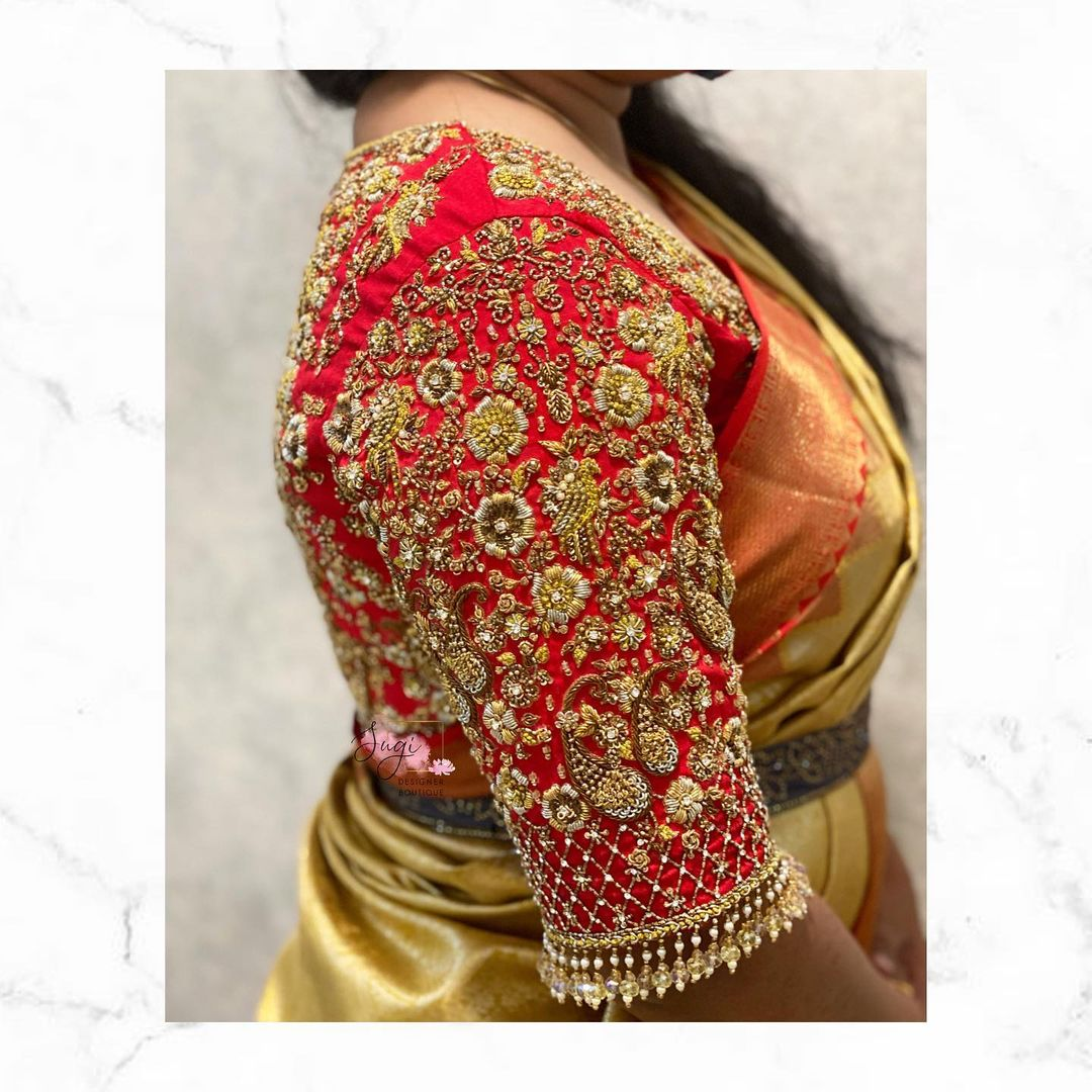 Stunning red color bridal blouse sleeve with floral hand embroidery gold thread and bead maggam work.  2021-09-19